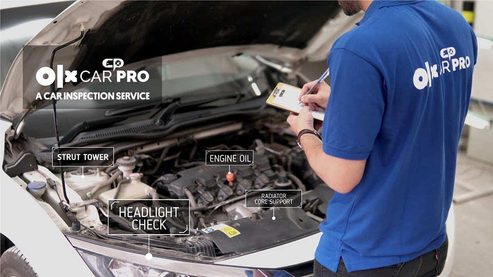 A CarPro team member standing infront of a car's open bonnet and inspecting the engine during a car inspection.