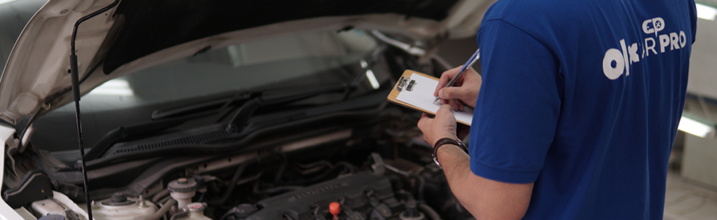 A carpro inspector is carrying out a car inspection of a car on the cars engine.