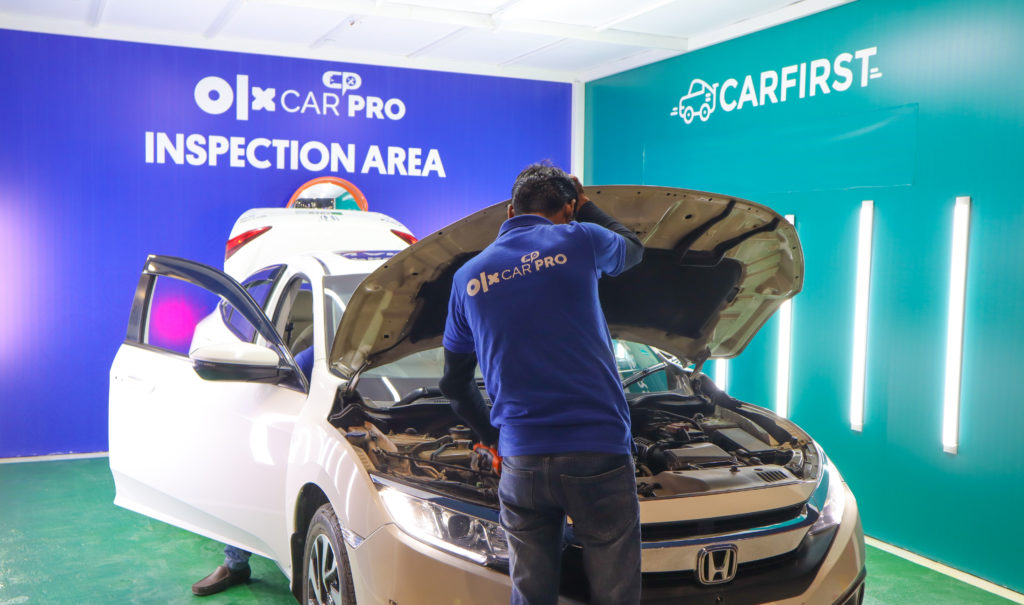 OLX CarPro Inspector carrying out a car inspection by opening the bonnet of a car at the facilitation center in Lahore.