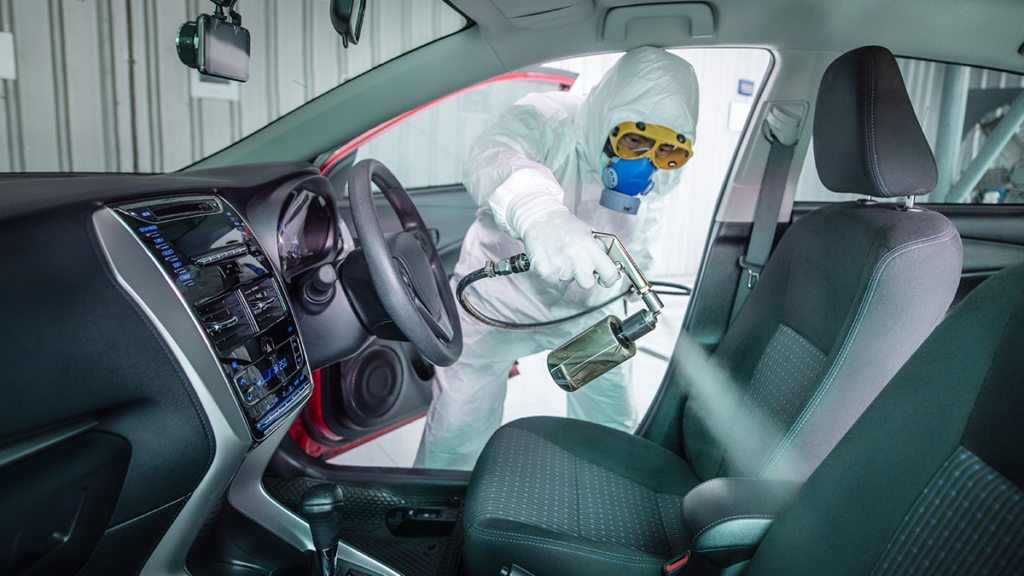 A generic image of a man disinfecting a car for a safe journey.