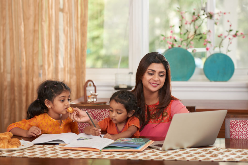 mother multitasking; working and teaching children