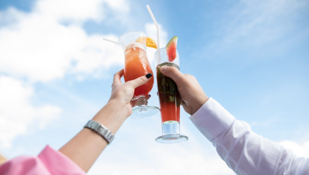 photograph-of-juice-glasses-in-hands-outside